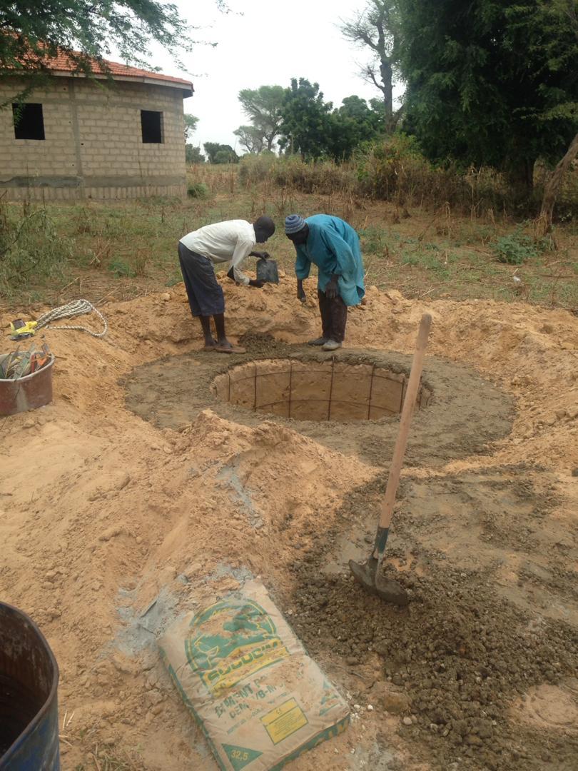 Travail du puits deuxieme jour: mise en place de la grille, betonnage du tour